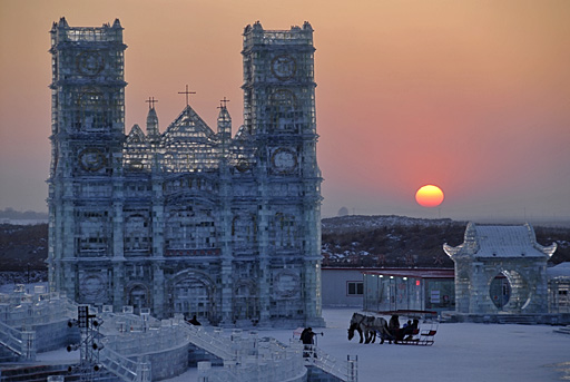 Cathedral of ice at Harbin International Ice and Snow Festival with wintry sunset in background.
