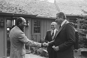 Anwar Sadat shakes hand of Israeli defense minister, Ezer Weizman, as Menachem Begin looks on, 1978